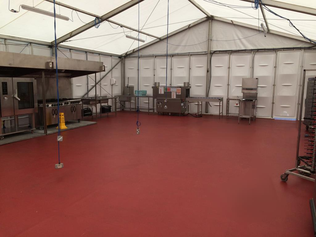 Medium sized rigid frame marquee during installation, demonstrating their capability to host sizeable kitchens.